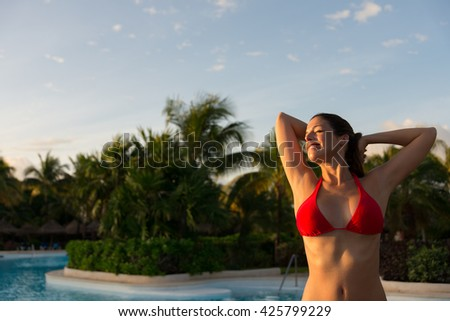 Woman enjoying relaxing tropical vacation at caribbean resort swimming pool. Female happy girl having fun at poolside. - stock photo