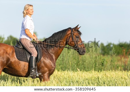 Woman enjoying riding horse in summer meadow.
