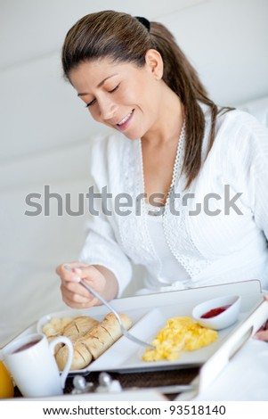 Woman enjoying room service and eating breakfast at a hotel - stock photo