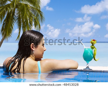 Woman enjoying sunny day at the swimming pool near the ocean - stock photo