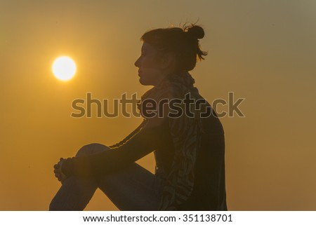 Woman enjoying the amazing sunset in Santorini on the top of a hill.