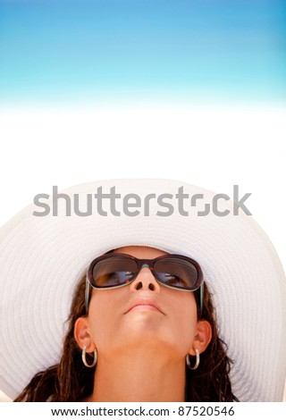 Woman enjoying the summer but protecting her skin with a hat and sunglasses - stock photo