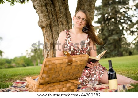 Woman enjoying the summer with a good book, picnic and bottle of wine - stock photo