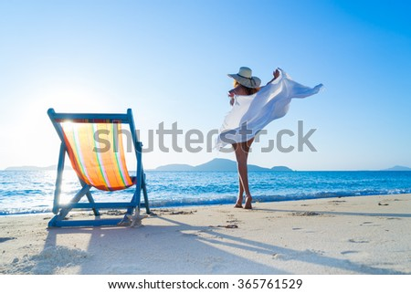 Woman enjoying the sun at the tropical beach - stock photo