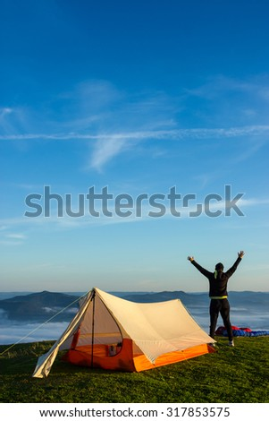 Woman enjoying the view with the arms up in the air after a night on the Tent - stock photo