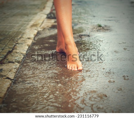 Woman enjoying tropical rain. Legs. - stock photo