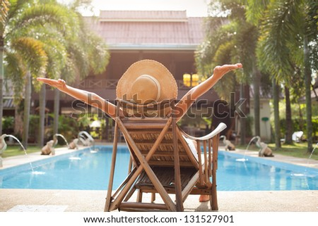 woman enjoying vacations near swimming pool - stock photo