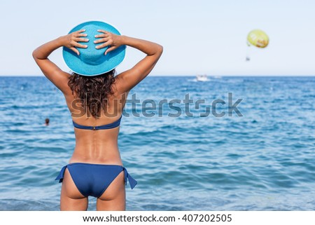 Woman enjoying warm summer day at the seaside.
