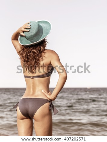 Woman enjoying warm summer day at the seaside. Vintage style. - stock photo