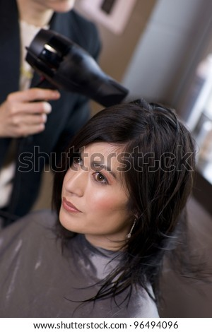 Woman Enjoys A Professional haircut style and blow dry at the salon - stock photo