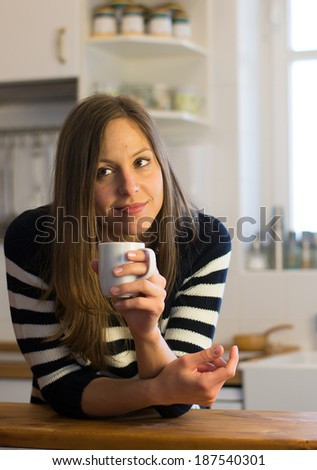 Woman enjoys fresh coffee in the morning with sunrise at home  - stock photo