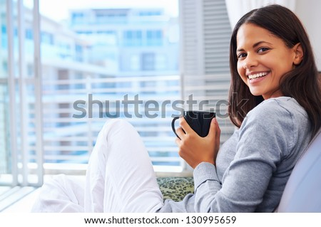 Woman enjoys fresh coffee relaxing at home on the sofa couch - stock photo