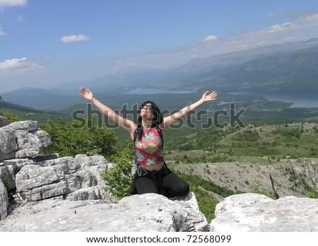 Woman enjoys sun in mountains on hiking - stock photo