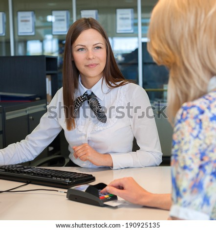 Woman entering security details for credit card in bank - stock photo
