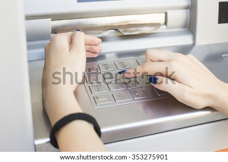 woman enters a PIN code and withdraws money from an ATM - stock photo