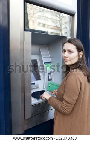 woman enters the PIN number at the ATM