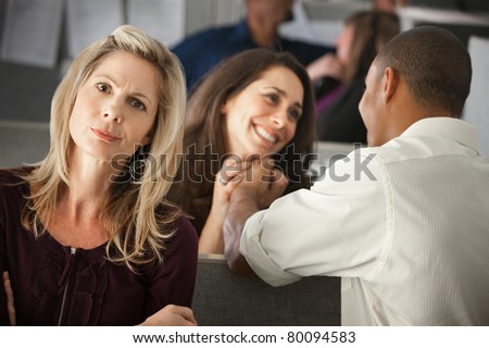 Woman envies coworker's love affair at in another cubicle - stock photo