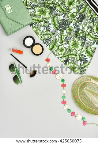 Woman essentials. Fashion lady summer outfit, girl clothes set, cosmetics, makeup accessories. Stylish handbag clutch, green dress, necklace, sunglasses. Unusual overhead, top view on gray - stock photo