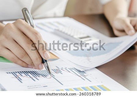 Woman evaluating charts and documents on paper