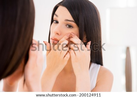 Woman examining face. Beautiful young woman examining her face while looking at the mirror - stock photo