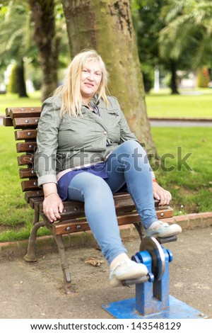 Woman exercise bike in the park. - stock photo