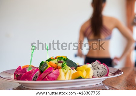 Woman exercise in the kitchen with fruits on the table at home. - stock photo