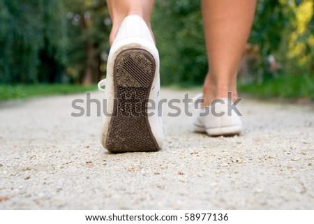 Woman exercise walking outdoors, shoes closeup - stock photo