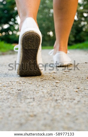 Woman exercise walking outdoors, shoes closeup. Runner or jogger training outside in summer nature, health and fitness - stock photo