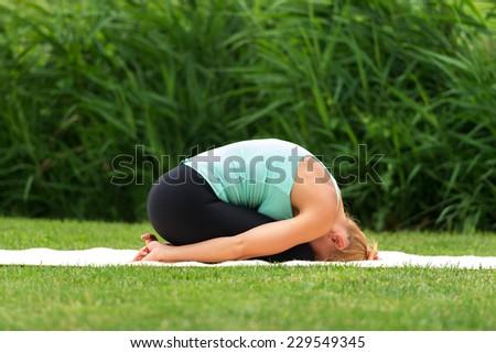 Woman exercise yoga asana child pose - stock photo