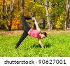 Woman exercises in the autumn forest yoga Ardha Chandra chapasana pose - stock photo
