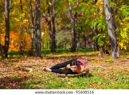 Woman exercises in the autumn forest yoga ashtavakrasana pose - stock photo