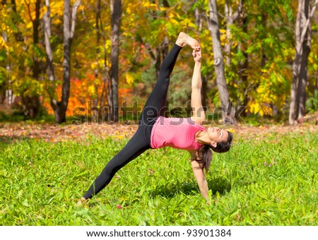 Woman exercises in the autumn forest yoga vasishthasana pose - stock photo