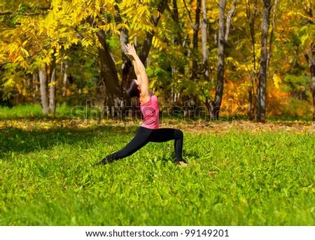 Woman exercises in the autumn forest yoga virabhadrasana pose - stock photo