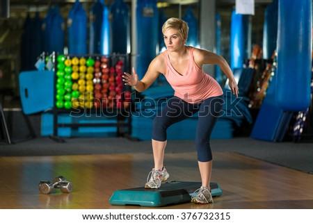 Woman exercising aerobic high endurance core cardio stepper class for weight loss calorie burn - stock photo