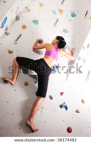 Woman exercising at a climbing wall in a gym - stock photo