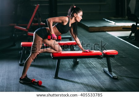 woman exercising dumbbell row at the gym - stock photo