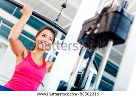 Woman exercising her arms and back at the gym on a machine - stock photo