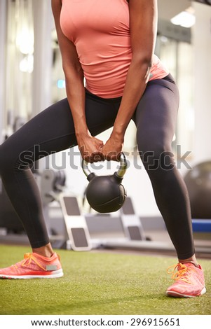 Woman exercising in a gym with a kettlebell weight, crop - stock photo
