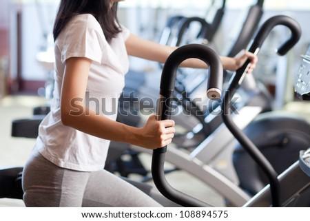 Woman exercising on a cardio machine - stock photo