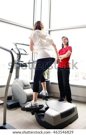 Woman exercising on cross trainer machine under personal trainer supervision