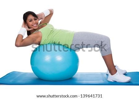 Woman Exercising On Pilates Ball Over White Background - stock photo