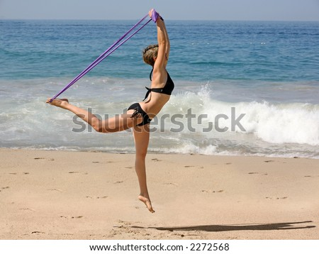 Woman Exercising on the beach with a rubber band - stock photo