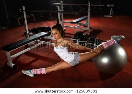Woman exercising Pilates ball workout posture in fitness club - stock photo