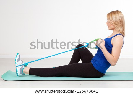 Woman exercising with a rubber band - stock photo