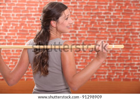 Woman exercising with a stick - stock photo