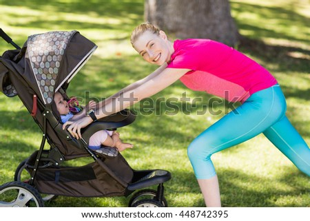 Woman exercising with baby stroller in park - stock photo