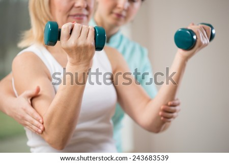 Woman exercising with dumbbells in rehabilitation clinic - stock photo