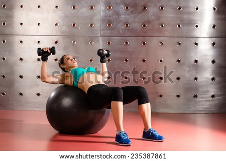 Woman exercising with stability ball and dumbbells - stock photo