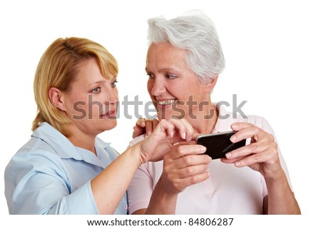 Woman explaining smiling senior woman a smartphone