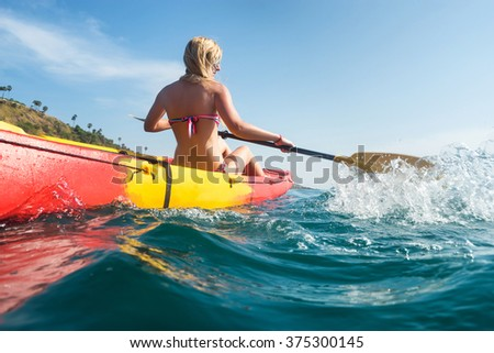 Woman exploring calm tropical bay  by kayak. - stock photo